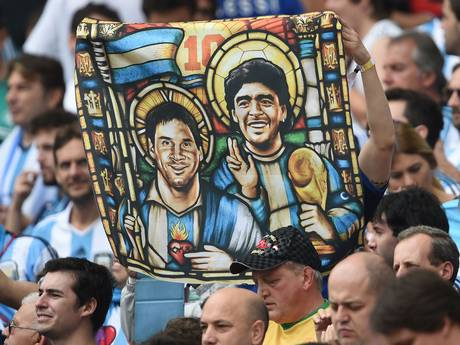 An Argentina's fan holds an image of Argentina's forward Lionel Messi and former footballer Diego Maradona as Saints
